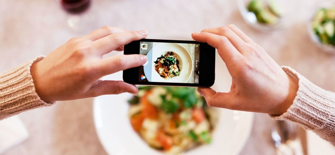 Woman taking overhead photo of dinner